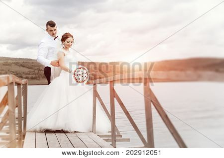 Young Wedding Couple Enjoying Romantic Moments Outside Next To The Pier, On A Summer Meadow.  Weddin