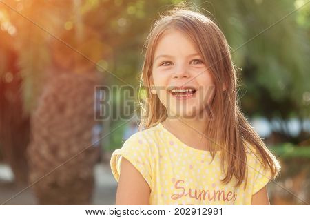 Beautiful cheerful little girl is smiling and looking at the camera. The child enjoys the sunny summer day. Beautiful smile. Portrait in the backlight.