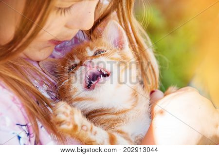 Little Girl With A Red Kitten In Hands Close Up.  Bestfriends. Interaction Of Children With Pets.