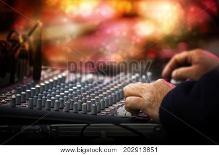 Working sound control panel or mixing console in front of the stage at a music festival concert selected focus narrow depth of field blurry background bokeh