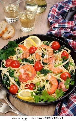 Pasta with fried prawns peas tomatoes and spinach in a frying pan on a table with cider glasses.