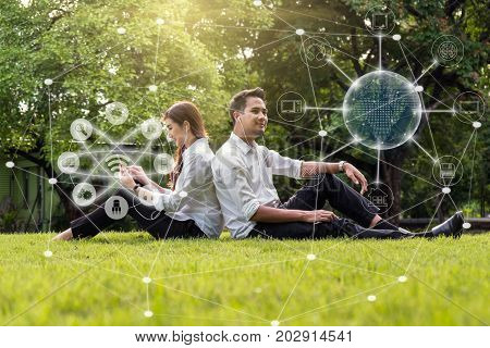 Happy asian couple using and listening the song and using the social network via smart mobile phone for online shopping with omni channel in the park lifestyle and technology concept