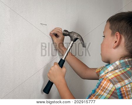 little boy is hammering a nail into the wall with a hammer. Funny child 6 years old helps in repairing a new family home. Baby with nails and a hammer
