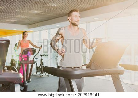 Young happy handsome man with tattoo in fitness club. Cardio workout, running on treadmill. Healthy lifestyle, guy training in gym. Flare effect