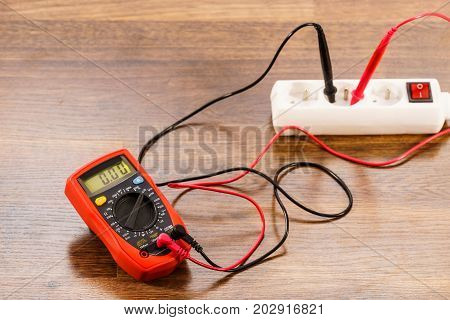 Measurement of voltage in electrical socket extension cord with multimeter on wooden floor background