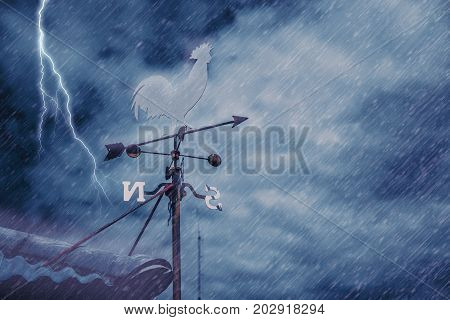 Wind Vane On House Roof With Background Of Storm Raining Windy Black Cloudy Dark Sky With Thunderbol