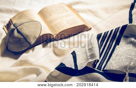 JERUSALEM, ISRAEL - DECEMBER 21: Jewish ritual objects, elements of prayer vestments, Talit, Kippah and Siddur - jewish prayer book. Toned image in Jerusalem, Israel on December 21, 2016