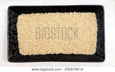 White sesame seed in ceramic black plate isolate on white wood has clipping paths.