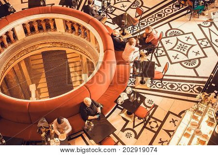 VIENNA, AUSTRIA - JUNE 10, 2016: People relaxing and drinking coffee inside the cafe of Kunsthistorisches Museum with historical furniture on June 10, 2016. Musem was opened in 1891