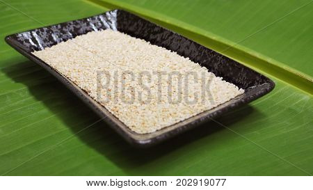 White sesame seed in ceramic black plate on background banana leaf green color and extra close up macro photo dimension perspective  focus select at center of picture
