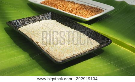 White sesame seed in ceramic black plate and roasted in white plate on background banana leaf green color and perspective macro photo focus select at center of plate black color around are blur.
