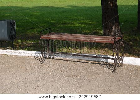 Wooden bench in the park with a shod iron ornament
