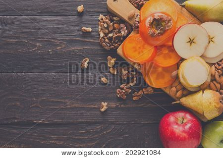 Healthy food - wood board with cut organic raw fruits on wooden background. Top view of sliced ingredients for fruit salad or snack - apple, pear, nuts, persimmon. Flat lay, copy space
