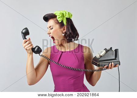 Young Woman Screaming Into A Phone .