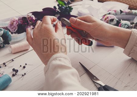 Master making handmade jewelry, woman pov. Needlewoman workplace with plastic beads, flowers and tools for creating accessories, filtered image