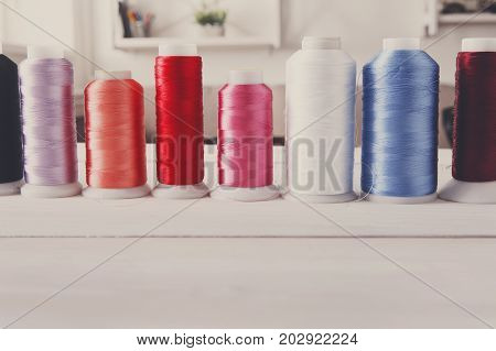 Colorful thread spools on wooden table close up. Sewing string, copy space for text, filtered image. Art, handicraft concept