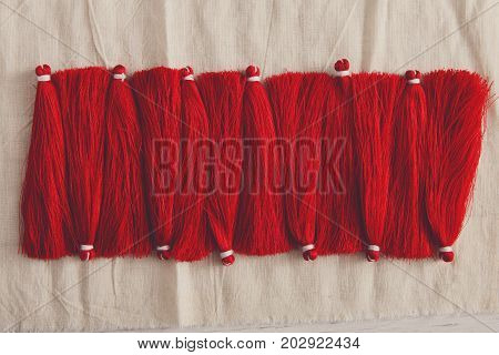 Red tassels line close up. Woman handicraft, filtered image. Art, creativity, hobby, home workshop concept