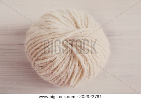 Needlework and handicraft concept. White soft ball of yarn for knitting handmade cloth close up, filtered image