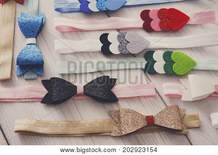 Set of colorful elastic decorated headbands. Bright handmade hair accessories with felt bow and star decoration, filtered image. Beauty, fashion, style concept poster