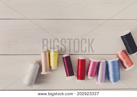 Colorful thread spools on wooden table flat lay. Sewing string spools, copy space for text, filtered image. Art, handicraft concept