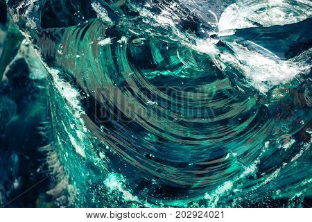a piece of broken glass with semicircular cracks and splits, a combination of a shade of blue, green, white and gray, close-up, large texture, background