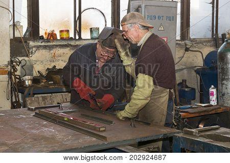 KHARKOV, UKRAINE - 8 JUNE 2017 : Metalworking shop workers work behind machines and apparatuses to create steel structures.Kharkov. Ukraine-2017
