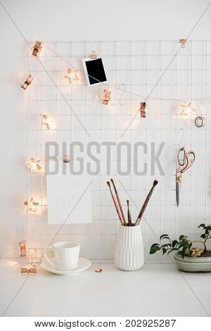 Clean and tidy workspace, white table top and office organizer with lights. White home office room interior, bloggers workplace. Poster mockup.