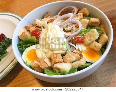Simple caesar salad with croutons in a bowl on wood table.