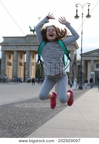 little girl makes a big leap in the Berlin square in front of the Brandenburg Gate