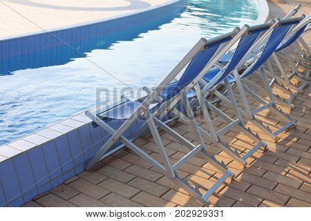 Empty Deck Chairs On The Pool Edge Of The Spa