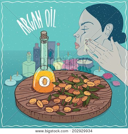 Glass Decanter of Argan oil and fruits of Argania spinosa plant. Girl applying facial mask on face. Natural vegetable oil used for skin care