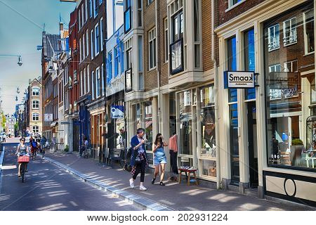 AMSTERDAM, NETHERLANDS - MAY 8, 2016: A typical Amsterdam street with old dutch buildings and people in Old Town of Amsterdam, Netherlands.