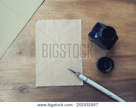 Blank old sheet of paper with a dip pen an inkwell and an envelope on a worn wooden background (view from the top or flat lay) retro style