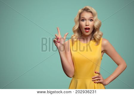 Pop art portrait of beautiful woman pointing finger on copyspace.