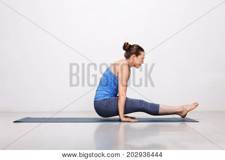 Woman doing Hatha asana Utpluti dandasana - lifted stuff pose on yoga mat on yoga mat in studio on grey bagckground