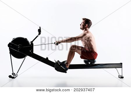 Man Using A Press Machine In A Fitness Club. Young man doing an exercise on its feet in the simulator. side view
