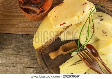 Sliced hard cheese on the kitchen board. Production of cheeses on the farm. Different types of homemade cheese.