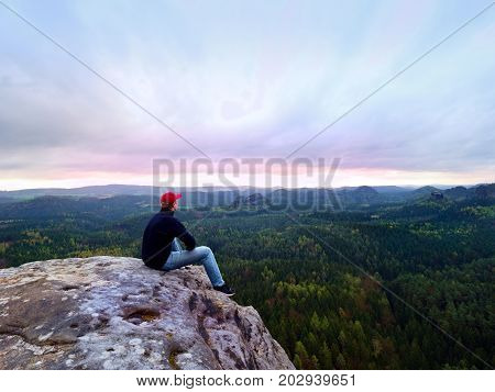Man Tourist Sit On Peak Of Mountain. Travel Mountain Scene. Hiker Take A Rest  Alone On The Mountain