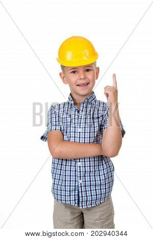 Handsome happy future builder dressed in blue checkred shirt, grey jeans and yellow helmet, gesturing on white background
