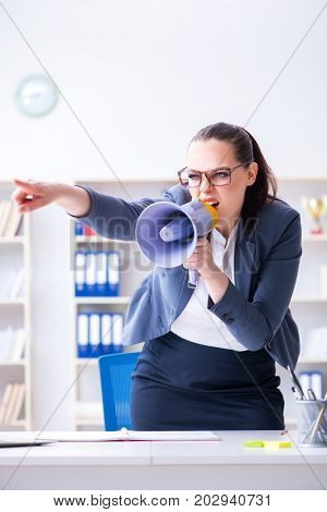 Angry businesswoman yelling with loudspeaker in office