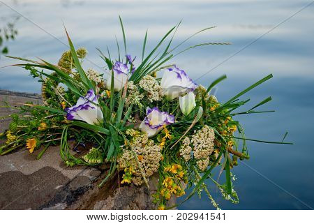 One beautiful big bouquet of a wreath of fresh wildflowers and green grass lies on the rocks of a parapet wall of rocks against the background of the Ukrainian river Dnepr on the feast of Ivan Kupala