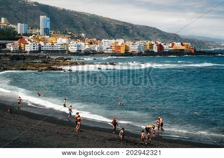 Puerto de la cruz Tenerife Canary islands Spain - May 30 2017: People sunbathing and relaxation in Playa Jardin. One of the best black sand beaches in Tenerife