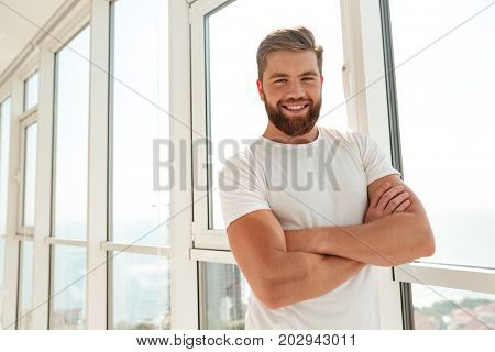 Happy bearded man with crossed arms standing near the window at home and looking at the camera