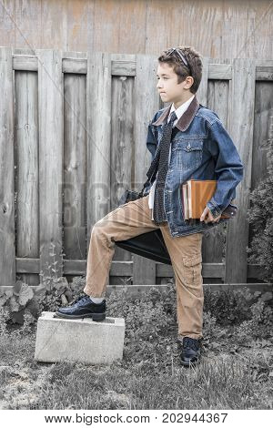 Trendy Preteen Boy Posing In Vintage Style Denim And Corduroy Clothing, Leather Satchel, Holding Boo
