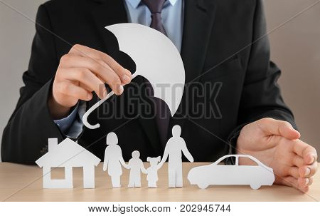 Man holding umbrella over paper silhouette of family, house and car on table. Insurance concept