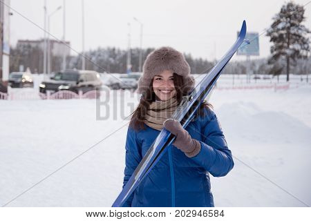 Young smiling woman walks through a ski Lodge with skis