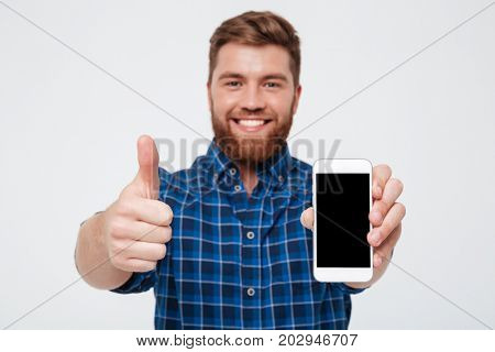 Smiling Bearded man in checkered shirt showing blank smartphone screen and showing thumb up at camera over gray background. Focus on smartphone