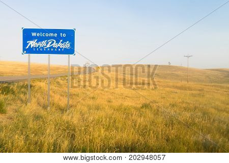 The scene is all blue and yellow at an entrance to North Dakota Road Sign
