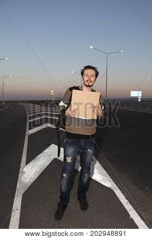 21 years old handsome man hitchhiking on the road