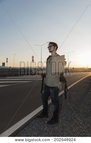 21 years old man hitchhiking on a highway